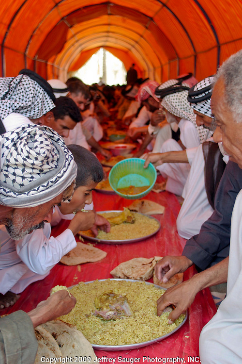 Guests and tribal chiefs eat first in one of two Motheff. The main course for lunch onsists of boiled lamb and rice at the Al-kasid family's Istikbal, or homecoming, in their home village Suq ash Shuyukh about 20 miles southeast of Nasiriyah, Iraq, Tuesday, July 29, 2003. Family members eat seperately after they've made sure the guests have been taken care of...The Al-kasid family fled Iraq after the Gulf War and their part in the uprising against Saddam Hussein in 1991, spent 3 years in Rafa, Saudi Arabia and finally settled in Dearborn, MI. The family hasn't been home to Iraq in 13 years.