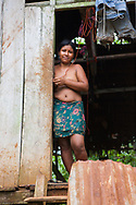 An Embera woman smiles from the front door of her stilted house, Churoco, Darien Province, Panama.