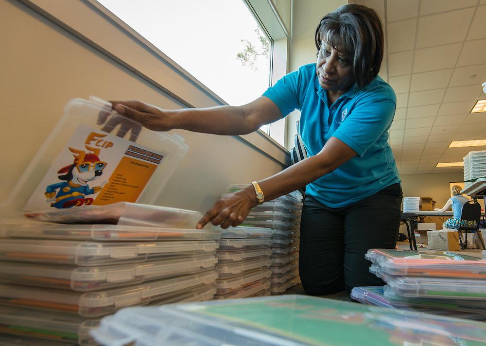 Volunteers prepare Focused Literacy Involvement Program (FLIP) boxes at the Children's Museum, October 21, 2014.