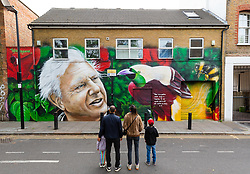 """© Licensed to London News Pictures. 06/05/2019. London, UK.  A family look at the new David Attenborough Mural painted on the side of a house in St Matthew's Row, east London.  The mural by urban artist, Jerome shows natural historian, David Attenborough with a message, """"There is no question climate change is happening. The only arguable point is what part humans are playing in it"""". Photo credit: Vickie Flores/LNP"""