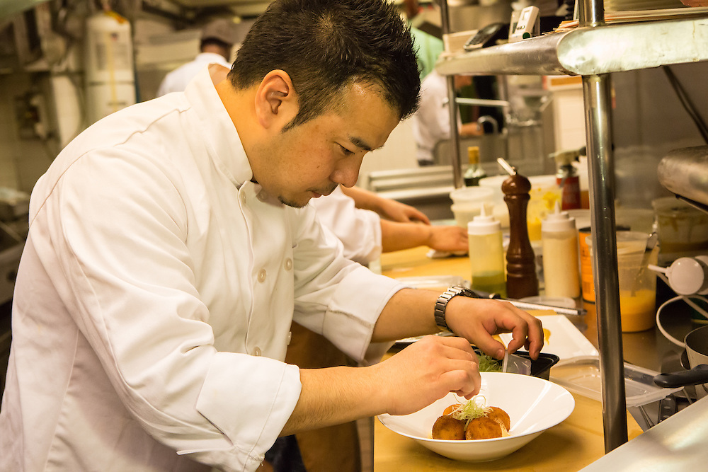 Chef Takanori Akiyama at work in the kitchen at SakaMai garnishing lobster croquettes.