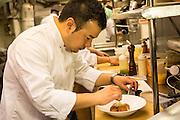 Chef Takanori Akiyama at work in the kitchen at SakaMai garnishing lobster croquettes.