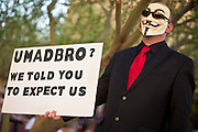 "22 OCTOBER 2011 - PHOENIX, AZ:    An Occupy Phoenix protester with a Guy Fawkes mask stands across the street from a bank in Phoenix Saturday. The demonstrations at Occupy Phoenix, AZ, entered their second week Saturday. About 50 people are staying in Cesar Chavez Plaza, in the heart of downtown. The crowd grows in the evening and on weekends. Protesters have coordinated their actions with police and have gotten permission from the city to set up shade shelters and sleep in the park, but without tents or sleeping bags, which is considered ""urban camping,"" instead protesters are sleeping on the sidewalk.      PHOTO BY JACK KURTZ"
