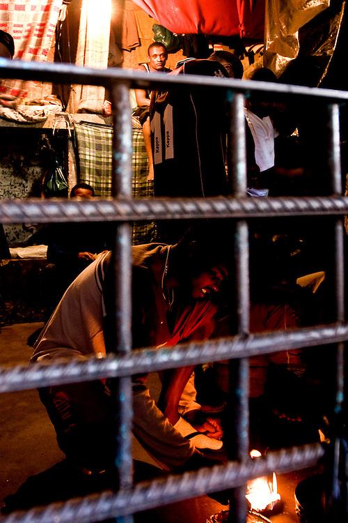 Ouro Preto _ MG, 16 Janeiro de 2008..FOLHA SAO PAULO.ESPECIAL - CRISE CARCERARIA EM MINAS..Carceragem municipal de Ouro Preto. Apesar do estado ja citar que a cadeia ja esta em obras, ainda apresenta muitos problemas...Grandes falhas de seguranca: Somente dois os policiais cuidam da cadeia, um civil (turno de 24 horas) e um militar (turno de 8 horas). SuperlotaÌão 170 presos, cuja capacidade sao 80...Na imagem, um preso acende um fogo para esquentar uma marmita com comida...FOTO: BRUNO MAGALHAES / AGENCIA NITRO / FOLHA IMAGEM