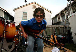 30 April 2006. New Orleans, Louisiana. Jazzfest . <br /> The first New Orleans Jazz and Heritage festival following the disaster of Hurricane Katrina. <br /> Just outside the entrance to Jazzfest local band Brotherhood of Groove with lead singer/guitarist Brandon Tarricone play for free in the garden of a house. One of the many parties to spring up around the festival.Photo ©Charlie Varley/varleypix.com<br /> All rights reserved.