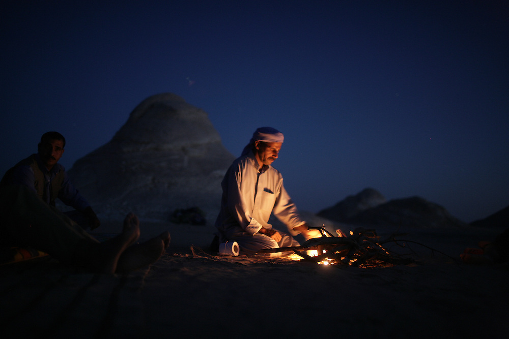 Abdalla, a bedouin in the Western Desert of Egypt, preparing food in the White Desert over an open fire. Photo by Wally Nell