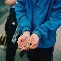 Belinda's son with some money that he is playing a game with, with his friends. His mother would like to be able to give her children pocket money but can't afford it. She lives on the Ford Estate in Sunderland where many families live below the poverty line.