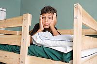 Tired multi ethnic boy lying on bed