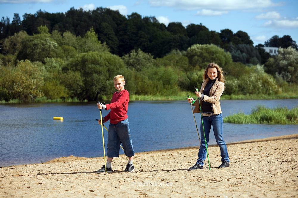 Teenage boy and young woman doing nordic walking