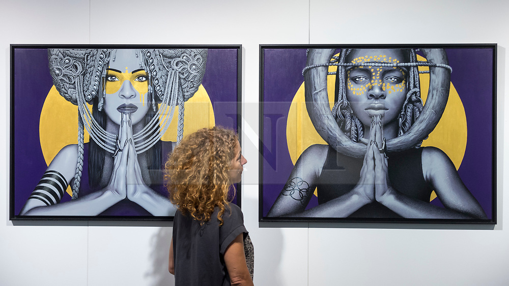 "© Licensed to London News Pictures. 04/10/2018. LONDON, UK. A gallery owner views ""Sun Goddesses"" by Fin DAC and Kevin Ledo.  Preview of Moniker Art Fair, taking place during Frieze Week at the Old Truman Brewery, near Brick Lane.  Now in its tenth year, the fair embraces contemporary urban art from emerging and established artists  This year, the show's theme is 'Uncensored', shedding light on social, economic and ecological issues, and is open 4 to 7 October.  Photo credit: Stephen Chung/LNP"