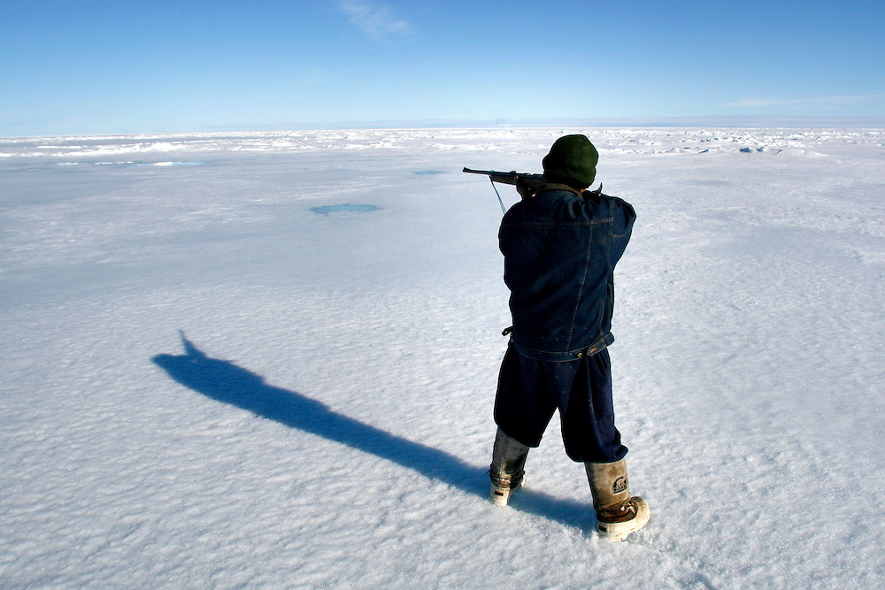 Sasa Samson, age 37, the best Inuit hunter in the Inuit town of Resolute Bay, Canada, hunts seals on Tuesday, June 12, 2007.  Sasa hunts seals for food, and his community uses every part of the seals, either eating the meat or using the hides to make warm clothes. Sasa often stands next to the breathing hole of the seal without moving for 30 minutes or more to capture the animal with with his hooked stick when it rises to the surface to breathe.   .. The traditional way of life in the Resolute Bay Inuit community is being threatened by rising temperatures.  The dangers of global warming, which have been extensively documented by scientists, are appearing first, with rapid, drastic effects, in the Arctic regions where Inuit people make their home.  Inuit communities, such as those living on Resolute Bay, have witnessed a wide variety of changes in their environment.  The ice is melting sooner, depleting the seal population and leaving them unable to hunt the animals for as long.  Other changes include seeing species of birds and insects (such as cockroaches and mosquitoes) which they have never encountered before.  The Inuit actually lack words in their local languages to describe the creatures they have begun to see.....