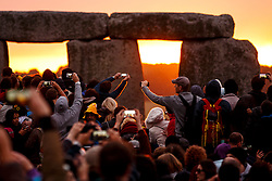 © Licensed to London News Pictures. 21/06/2015. Salisbury, UK. People take photos of the Summer Solstice sunrise at Stonehenge on June 21, 2015 in Wiltshire, England. Thousands of revellers gather at the 5,000 year old stone circle in Wiltshire to see the sunrise on the Summer Solstice dawn. The solstice sunrise marks the longest day of the year in the Northern Hemisphere. Photo credit: Tolga Akmen/LNP