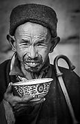 Pilgrim drinks from bowl during kora ( circuit) Jokhang Temple, Lhasa, Tibet