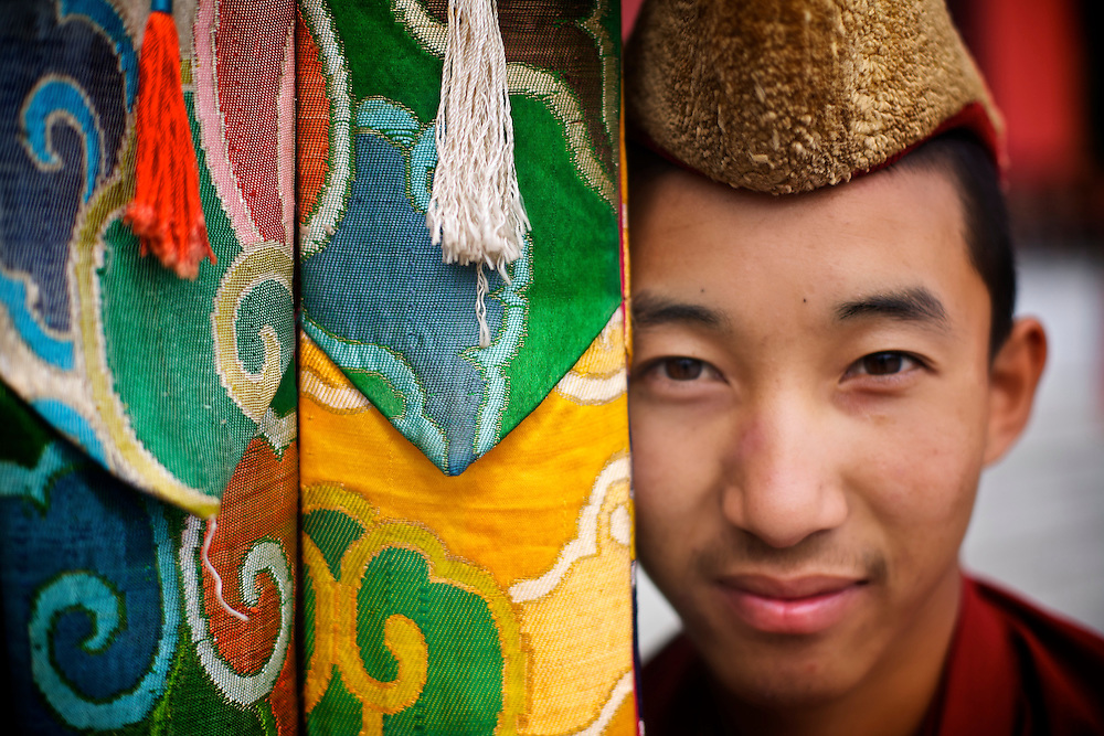 A young monk with traditional Tibetan hats in Kathmandu, Nepal.