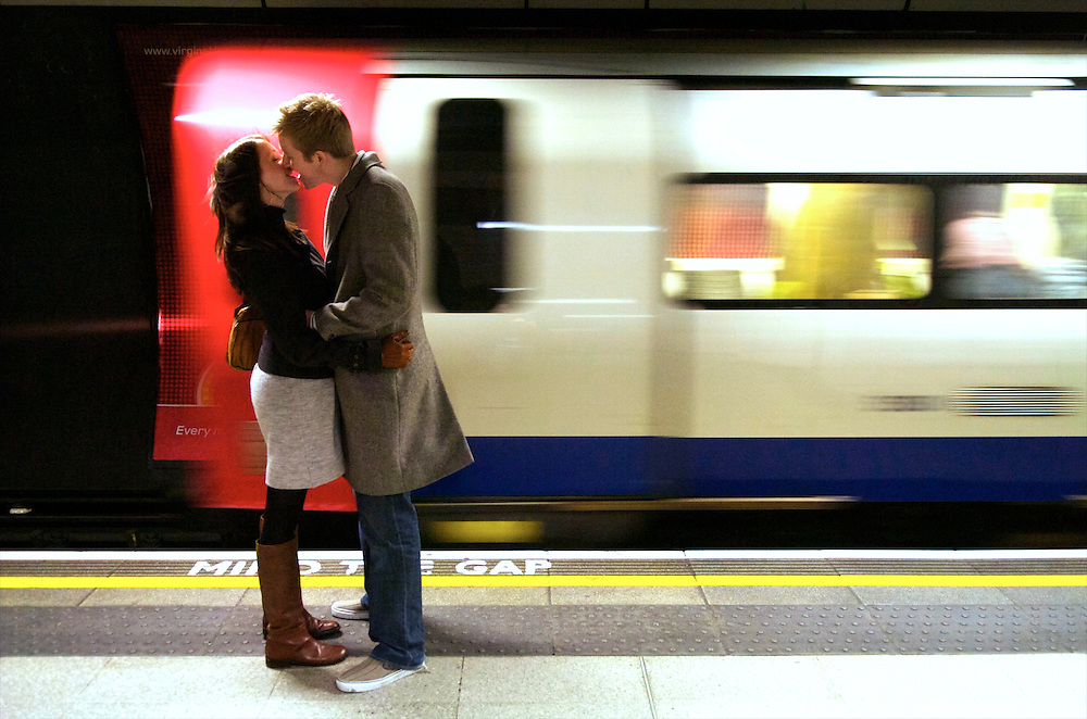 A couple kisses, missing their tube at London Bridge station.  The London Underground is the oldest subway in the world, carrying one billion passengers in 2008.