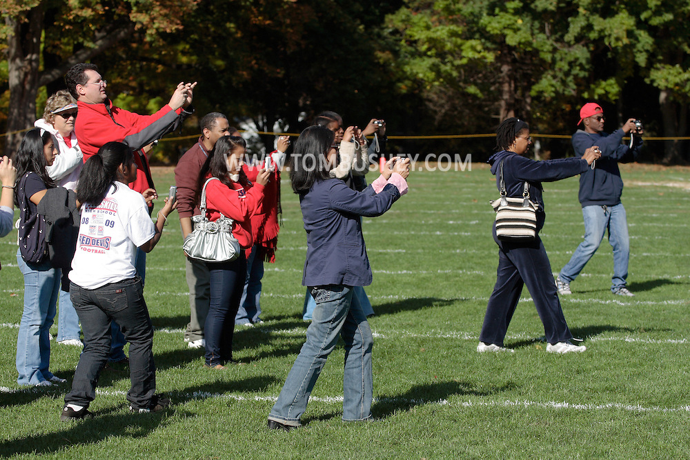 Peekskill, NY - Friends and family stand on the football field and take photographs of the  homecoming king and queen and members of their court at halftime of a game between Poughkeepsie and Peekskill in Peekskill on Oct. 18, 2008.