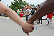 """People hold hands as David Phelps, Minister at Living Waters Kingdom Church, prays before the start of a """"Stop the Violence March"""" in Cedar Rapids on Saturday afternoon, May 19, 2012. The march was organized by a group of people fed up with the recent violence. About 90 people participated in the march with many people joining along the way. They plan on organizing a march monthly in various parts of town where there has been recent violence. (Stephen Mally/Freelance)"""