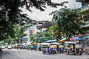 09 OCTOBER 2012 - BANGKOK, THAILAND:  A line of tuk-tuks (three wheeled taxis, common in Asia) wait for customers at the Bangkok Flower Market. The Bangkok Flower Market (Pak Klong Talad) is the biggest wholesale and retail fresh flower market in Bangkok. It is also one of the largest fresh fruit and produce markets in the city. The market is located in the old part of the city, south of Wat Po (Temple of the Reclining Buddha) and the Grand Palace.    PHOTO BY JACK KURTZ