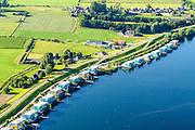 Nederland, Gelderland, Maasbommel, 23-08-2016; recreatiegebied De Gouden Ham, onderdeel van rivier de Maas met drijvende woningen aan de Bovendijk. De recreatiewoningen maken onderdeel uit van een complex van buitendijks gebouwde tweede huizen, die (gaan) drijven bij hoog water. De woningen zijn bevestigd aan meerpalen om verschillen in waterhoogte op te vangen. De amfbische huizen gaan alleen drijven bij hoog water. The Golden Ham recreation site, part of the river Meuse with floating houses on the Bovendijk (Upper Dike). The holiday homes are part of a complex of houses build outside the dike that will rise and fall with the water level. The houses are attached to bollards to compensate water level fluctuations. The amphibious houses will only float at high waters.<br /> aerial photo (additional fee required); <br /> luchtfoto (toeslag op standard tarieven);<br /> copyright foto/photo Siebe Swart