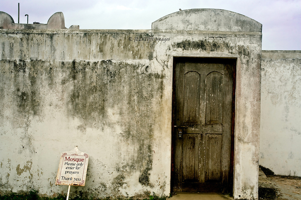 Entrance to a simple, poor, mosque in rural Zanzibar, with polite sign request: Please only enter for prayers. Thank you.