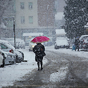 A woman walking with difficulty on icy roads of Turin.