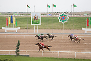 Horse racing at the City Hippodrome in Ashgabat on the occasion of National Turkmen Horse Day. A portrait of the Turkmenistan President Gurbanguly Berdimuhamedow, the national emblem, and national flags flank the racecourse. Riders compete for cars and domestic appliances as prizes.