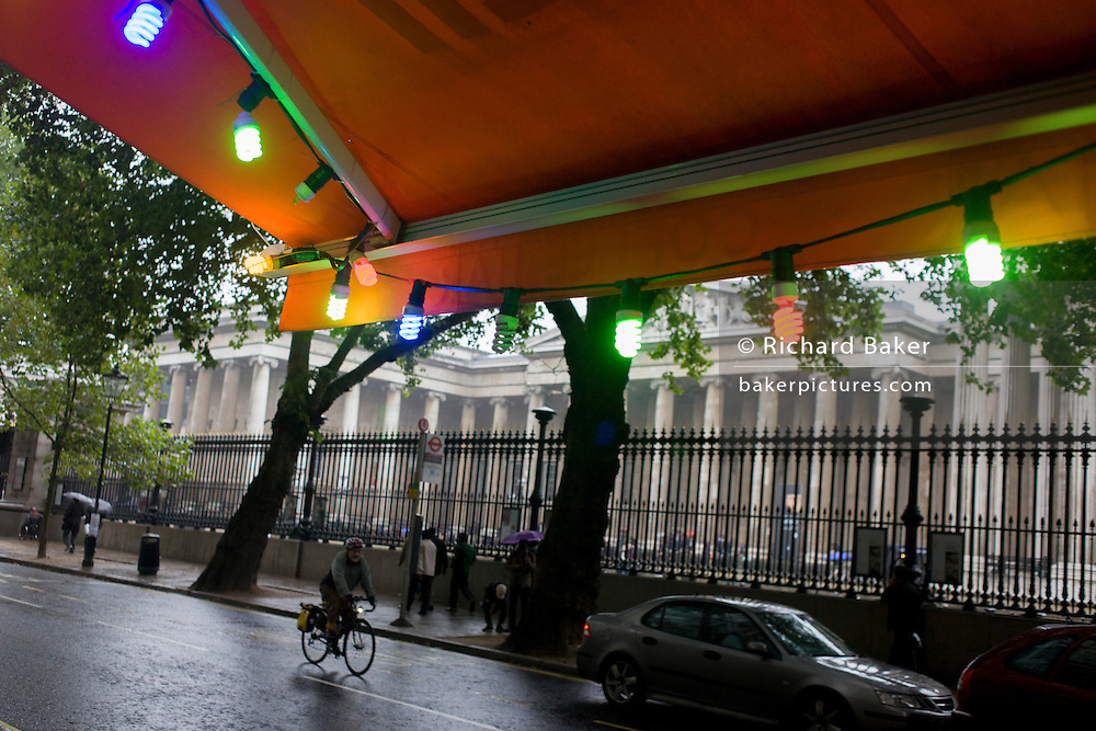 A cyclist pedals past coloured lights during damp, gloomy weather opposite the British Museum in central London.