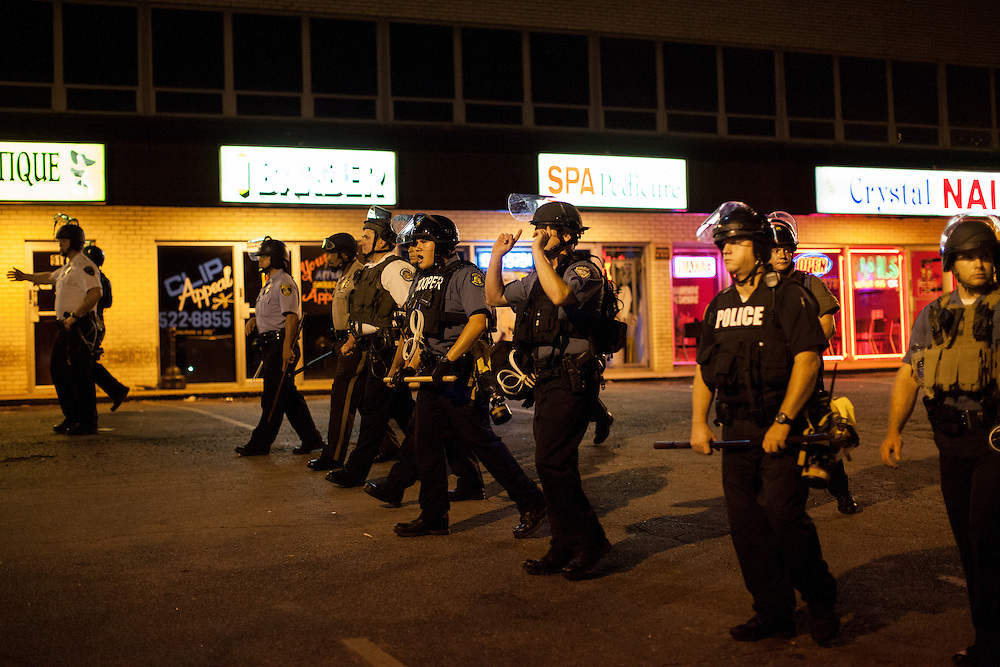 Police officers begin to advance down West Florissant Avenue in an attempt to break up the growing crowd of demonstrators. Protests have been ongoing in Ferguson, Missouri since the shooting death of Michael Brown, the eighteen-year-old unarmed teen killed by police on August 9, 2014.