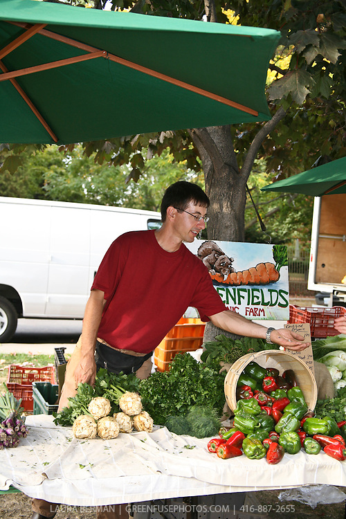 Lorenz of Greenfields takes a break form the farm and tends the table at Riverdale Organic farmers' market in Toronto, Canada