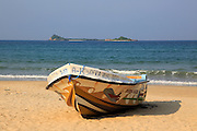 Boat on tropical beach at Nilavelli, Trincomalee, Sri Lanka, Asia with Pigeon Island in background