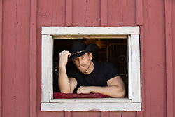 rugged cowboy looking out a barn window