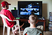 Talon Shannon, 15, (left) and Drake Shannon, 11, (right) two of the three children of John Daniel Shannon, 48, a former US Army Senior Sniper, are playing a war game on X-Box inside their home in Westcliffe, CO, USA. Daniel retired here with his family after a serious brain injury inflicted by an insurgent sniper in Ramadi, Al Anbar Province, Iraq, on November 13th 2004. He fought during the Second Battle of Fallujah and was then moved to nearby Ramadi. Daniel lost his left eye and has multiple health issues because of his injury: memory problems, balance problems, he can't smell and taste well anymore, he suffers from PTSD, has  troubles with large crowds and city surroundings. This is the reason why he and his family moved to a quiet location on the Rocky Mountains. In 2007 Dan helped the Washington Post to uncover patients' neglect at the Walter Reed Army Medical Center; he also testified before Congress. Torrey, 42, his wife, is a freelance writer and a contributor for the Huffington Post; she's also campaigning to improve the situation of veterans' families.