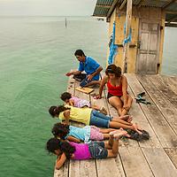 Latin family fishing on the pier. (Caye Caulker, Belize)