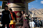 Local people in Leh are passing by a large praying wheel near the gate to the city where the Leh-Manali Highway beings...The Leh-Manali Highway is the main road connection between the remote mountainous region of Ladhak, with capital in Leh (3300m), and Manali, HP, a famous hill station 600 km north of New Delhi. Open only four months a year, it is the second-highest motorable road in the world crossing passes up to 5300 meters. It was constructed by the Indian Army in order to develop the surrounding areas as well as monitoring the nearby borders with Kashmir and China. Due to its beauty and increased accessibility, the road to Leh and Ladhak has recently become a must-see destination for local and international tourists leaving the scorching Indian plains..