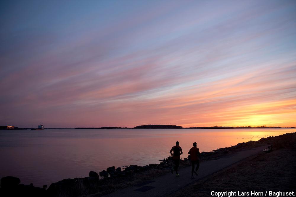 Solnedgang over Limfjorden med Egholm i baggrunden.Motionsløbere og Coaster sejler på fjorden..Foto: © Lars Horn / Baghuset.Date : 04.04.13