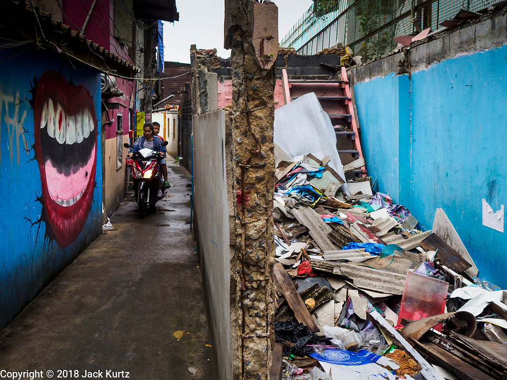 "22 MARCH 2018 - BANGKOK, THAILAND:  A motorcycle goes past a demolished home along Khlong Lat Phrao. Bangkok officials are evicting about 1,000 families who have set up homes along Khlong  Lat Phrao in Bangkok, the city says they are ""encroaching"" on the khlong. Although some of the families have been living along the khlong (Thai for ""canal"") for generations, they don't have title to the property, and the city considers them squatters. The city says the residents are being evicted so the city can build new embankments to control flooding. Most of the residents have agreed to leave, but negotiations over compensation are continuing for residents who can't afford to move.     PHOTO BY JACK KURTZ"