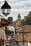 The Parroquia del Santuario de Guadalupe church rises above the tile roofs in Patzcuaro, Michoacan, Mexico.