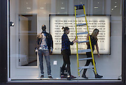 Window dressing designers carry stepladders inside a retailer's shop window in central London.