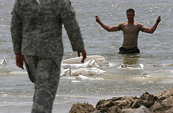 13 May 2010. Elmer Island, Lafourche Parish, Louisiana. <br /> Sgt George Achee of the Louisiana National guard inspects sandbags deposited earlier and already disappearing fast with the tide. Like King Canute before them, Louisiana National Guardsmen of the 922nd Horizontal Engineer Company, 769th Engineer Battalion fight a losing battle against mother nature as they battle against the strong currents to close the inland waterways from the ocean now depositing oil from the Deepwater Horizon catastrophe on the beaches. <br /> Photo credit; Charlie Varley/varleypix.com