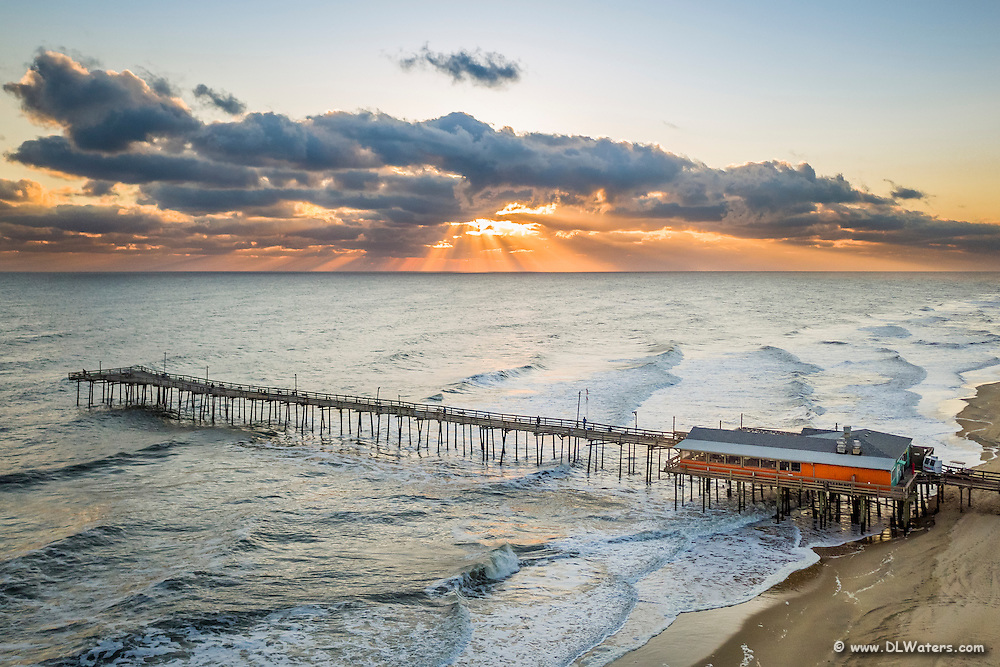 Aerial photo of the Outer Banks Fishing Pier at sunrise.
