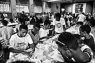 A large group of migrants having dinner in the soup kitchen managed by Caritas