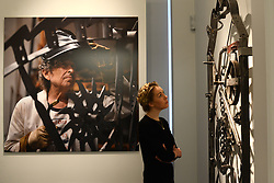 © Licensed to London News Pictures.14/11/2013. London, UK. A gallery employee looks at iron artwork by Bob Dylan during the Mood Swings exhibition preview at Halycon Gallery. The gallery present a major exhibition of new iron works by artist and musician Bob Dylan.Photo credit : Peter Kollanyi/LNP