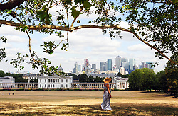 &copy; Licensed to London News Pictures. 01/08/2018<br /> Greenwich, UK. A woman shelters in the shade on Greenwich Park, in front of the city of London, as a heatwave is set to return to the UK. Photo credit: Grant Falvey/LNP