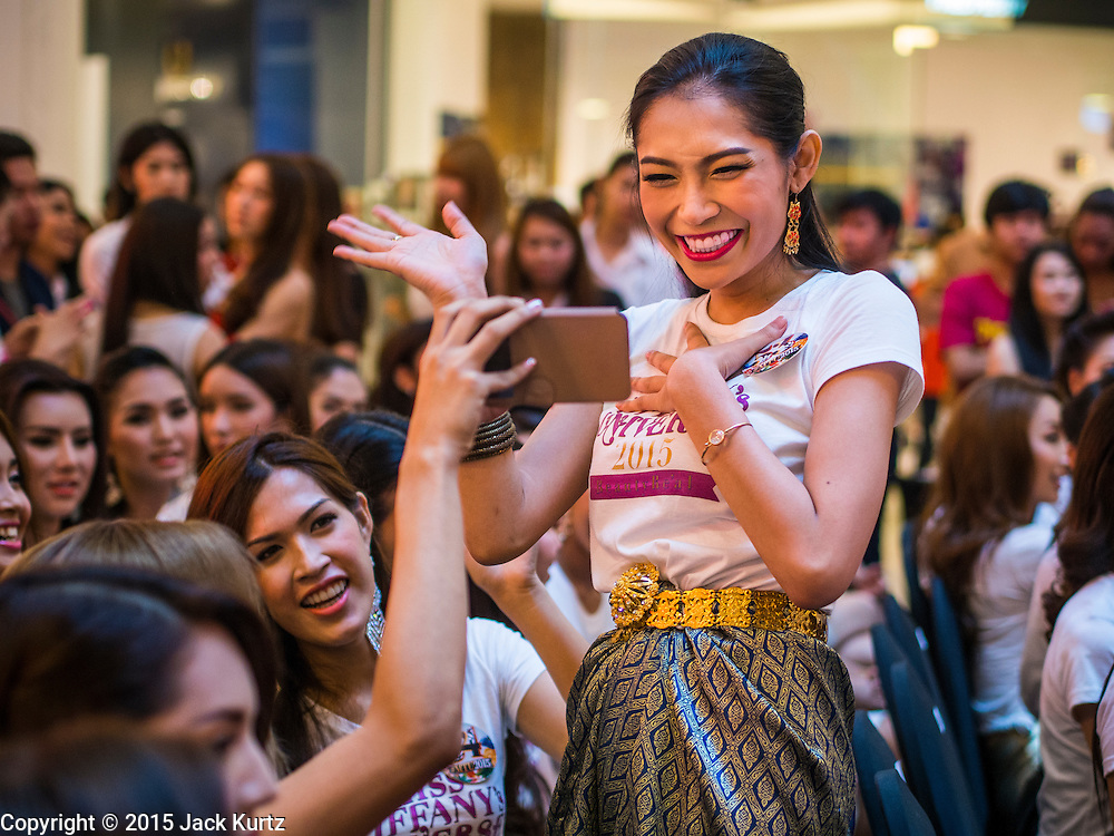 25 MARCH 2015 - BANGKOK, THAILAND: A contestant uses the video function on her smart phone to video chat with friends before going on stage in the first round of the Miss Tiffany's contest at CentralWorld, a large shopping mall in Bangkok. Miss Tiffany's Universe is a beauty contest for transgender contestants; all of the contestants were born biologically male. The final round will be held on May 8 in the beach resort of Pattaya. The final round is televised of the  Miss Tiffany's Universe contest is broadcast live on Thai television with an average of 15 million viewers.     PHOTO BY JACK KURTZ