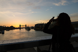 © Licensed to London News Pictures. 17/10/2014. London, UK.A woman photographs sunrise and blue sky over Tower Bridge in London this morning. Photo credit : Vickie Flores/LNP