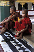 A Buddhist monk and his student visit Shwedagon, in Yangon.