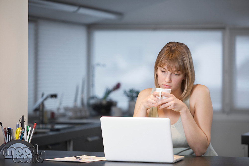 Young woman sits with cup at laptop in kitchen
