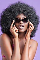 Portrait of young woman with fizzy hair wearing sunglasses over violet background