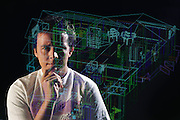 Virtual reality. Harry Marples, Computer Scientist, programming a system that will allow visitors a 3-D guided tour of a new building before it is even built. Plans for a proposed design are fed into a computer, which is capable of displaying them in sophisticated 3-D graphics. Thus the real building is presented by the computer as a virtual one. Visitors wearing special headsets fitted with video goggles and spatial sensors can move from room to room within the virtual space as if they were in the real world. Optical fibers woven into rubber data gloves provide a tactile dimension. Photo taken at the Computer Science Dept., University of North Carolina. Model Released Model Released (1990)
