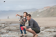 A young boy throws rocks into the ocean with his father at Lincoln City beach, Oregon.  Tossing rocks.